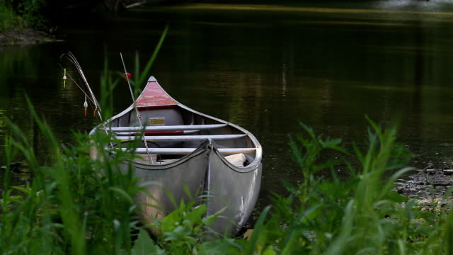 Fall River Canoe Closer HD 1080: A canoe adrift on the river bank. fishing rod stock videos & royalty-free footage