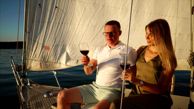 Fallen in love man and woman drinking wine during date on the yacht video