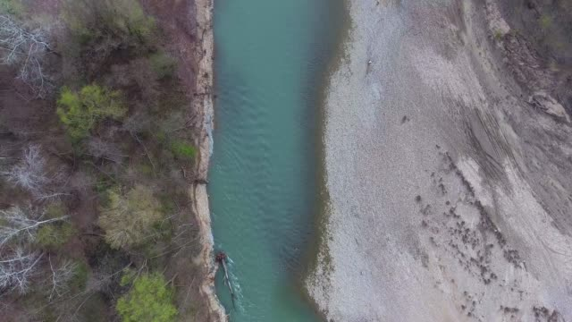 A fallen tree in a turquoise river. Top view