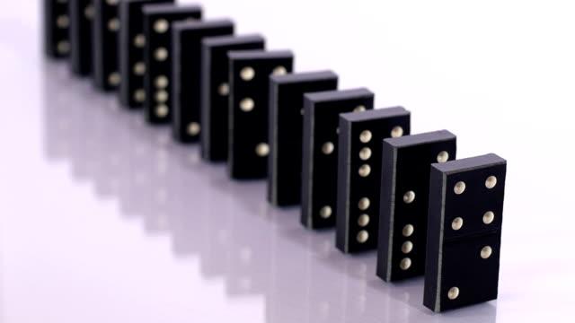 vídeos de stock e filmes b-roll de falling black dominoes in slow motion - continuidade