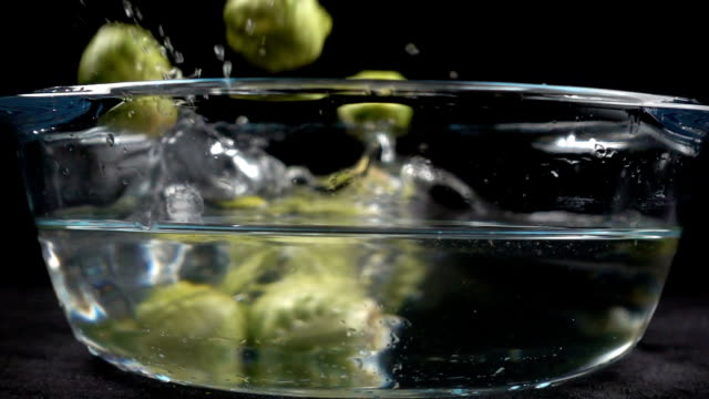 stockvideo's en b-roll-footage met dalende brussel aan glas pan met water splash - spruitjes