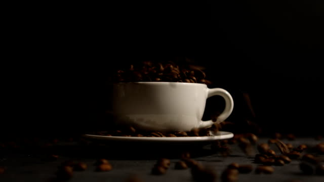 Falling coffee beans in coffee cup video
