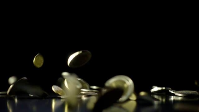 fallenden münzen zeitlupe dunklen hintergrund - euros cash stock-videos und b-roll-filmmaterial