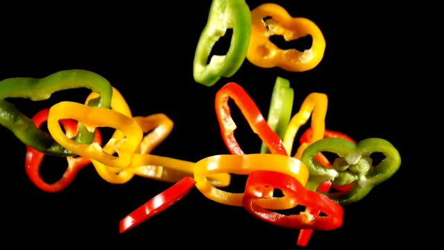 Falling colorful cuts of paprika rings, slow motion video