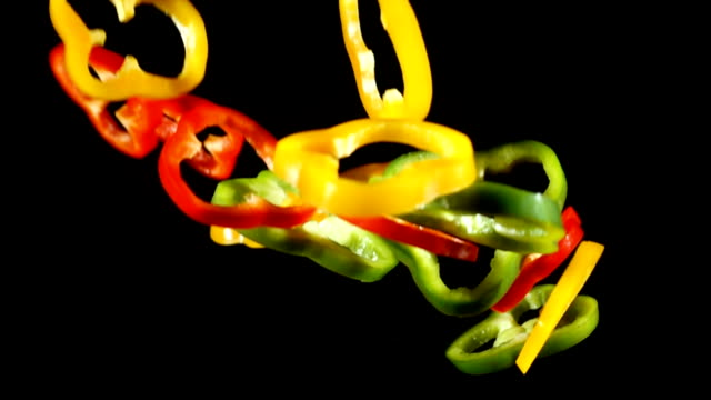 Falling colorful cuts of paprika, slow motion video