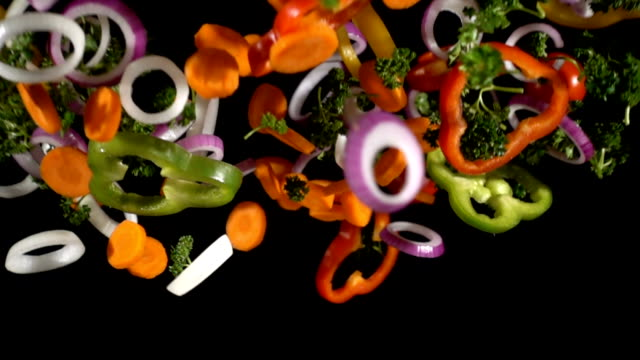 Falling cuts of colorful vegetables, slow motion video