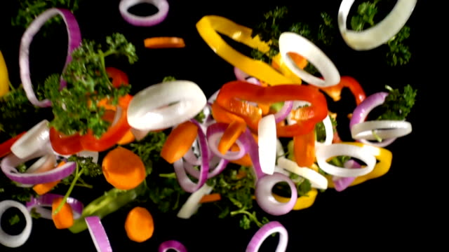 Falling cuts of colorful vegetables, slow motion Falling cuts of colorful vegetables isolated on black background, slow motion salad stock videos & royalty-free footage