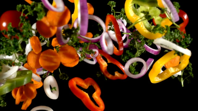 Falling cuts of plenty colorful vegetables, slow motion video