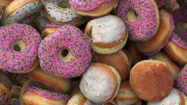 fallande olika donuts på en rosa bakgrund - confetti bildbanksvideor och videomaterial från bakom kulisserna