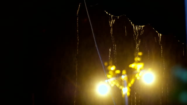 Falling drop of rain pouring from the roof with defocus street lamp in dark night video