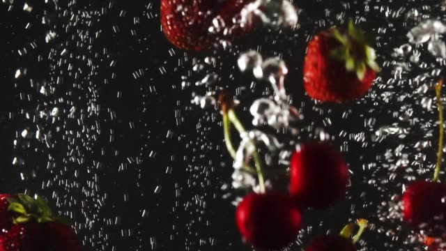 Falling fresh strawberries and cherries splashing into sparkling water on black background.