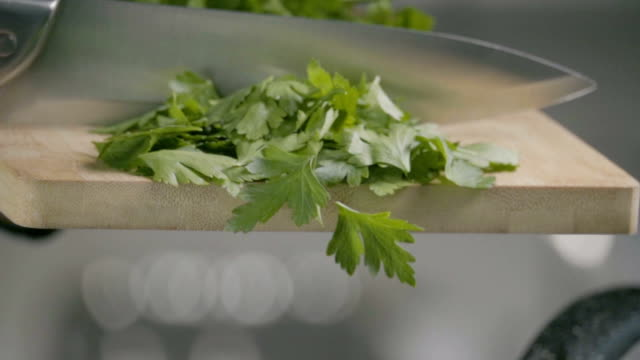 Falling of parsley into the frying pan. Slow motion 240 fps Falling of parsley into the frying pan. parsley stock videos & royalty-free footage