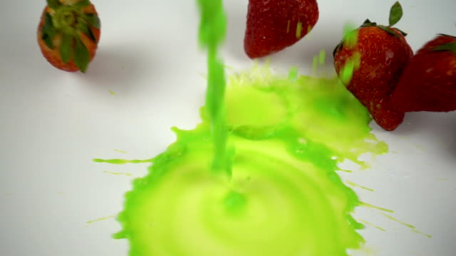 Falling paints with strawberries in slow motion.