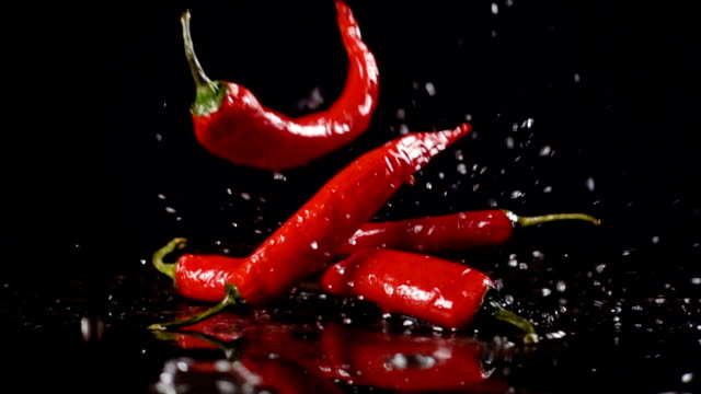 Falling red  chili pepper with water splash, slow motion Falling red chili pepper on black background with water splash, slow motion chili pepper stock videos & royalty-free footage