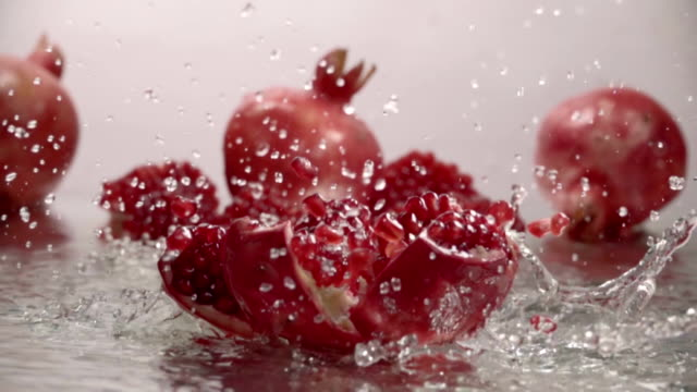 vídeos de stock e filmes b-roll de falling splitted pomegranate into the water . slow motion - romã
