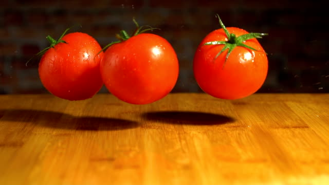 vídeos de stock e filmes b-roll de falling tomato on wooden table, slow motion - sauce tomatoes
