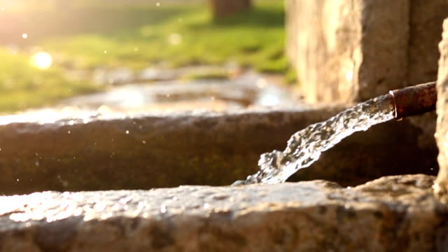Falling water from stone fountain video