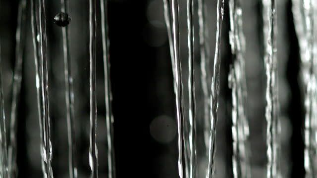 Falling water streams on black background video