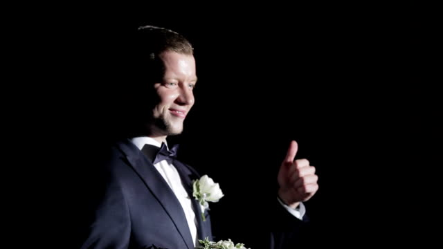 False emotions man showing side view black background close up. Man in formal clothing with bouquet of flowers showing thumbs up and unnatural smiling. Comedian actor plays role performance in theatre video