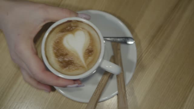 famale hand mit einer tasse kaffee und legt wieder auf teller aus der nähe. - cappuccino stock-videos und b-roll-filmmaterial