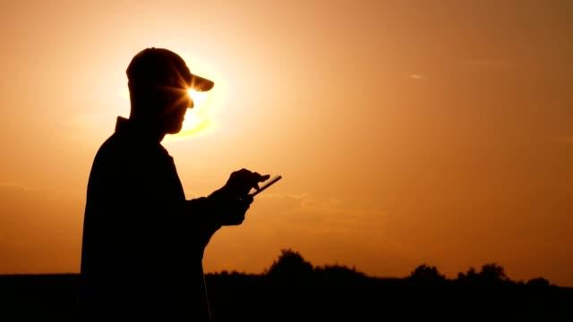 famer uses digita tablet  at sunset - efficacia video stock e b–roll