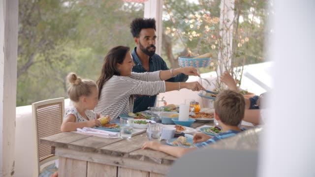 Familias disfrutando de comida al aire libre en la terraza juntos - vídeo