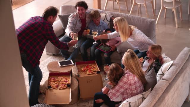 ご家族連れのお客様にリラックスできるソファー、ピザやワインのテイクアウト - 居間点の映像素材/bロール