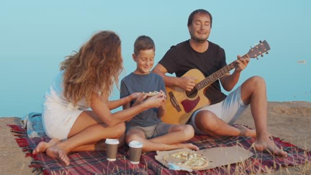 Familie actief communiceren terwijl picknick op een heuvel en het hebben van een hapje met koffie en pizza video