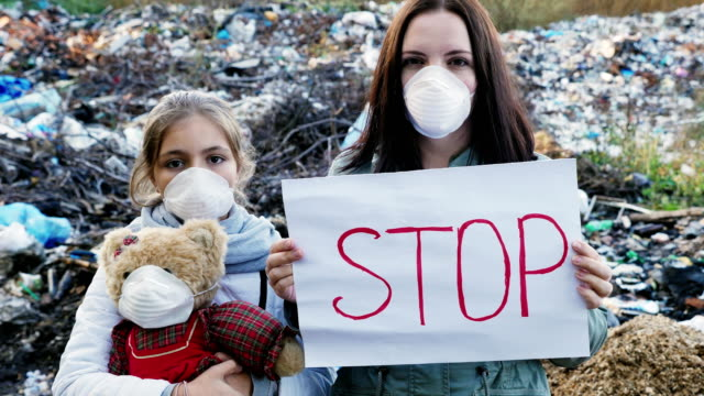 Family activists with Stop poster on waste dump Mom and daughter are activists in respirators with Stop poster on the background of a mountain of garbage. Static outdoors shot. Pollution and Environmental Contamination ecosystem stock videos & royalty-free footage