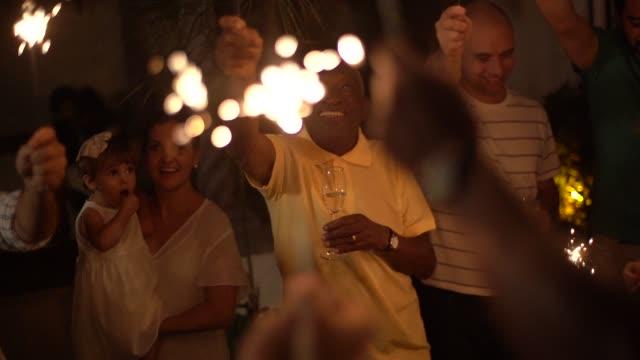 stockvideo's en b-roll-footage met familie en vrienden vieren new year party met sparkler thuis - buren