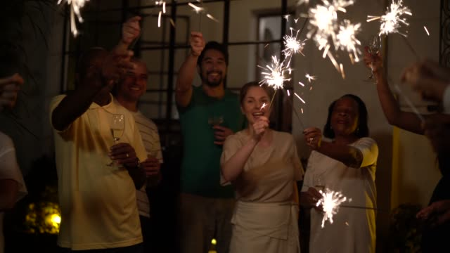 family and friends celebrating new year party with sparkler at home - new years stock videos & royalty-free footage