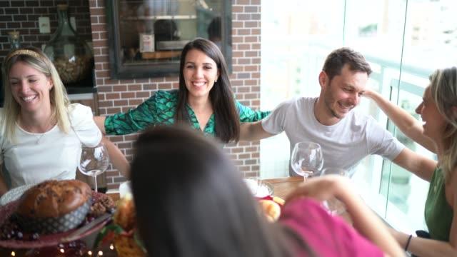 rodzina i przyjaciele zjedli się przy stole w czasie świąt bożego narodzenia - miesiąc filmów i materiałów b-roll