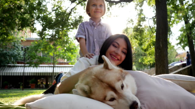 family and pet, young mother and son smile with husky dog in park video