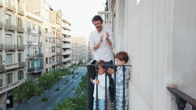 family applauding to the medical staff from the balcony for covid-19 - battere le mani esprimere a gesti video stock e b–roll