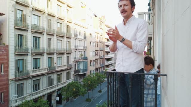 Familie applaudiert dem medizinischen Personal vom Balkon für COVID-19. Slo Mo. – Video
