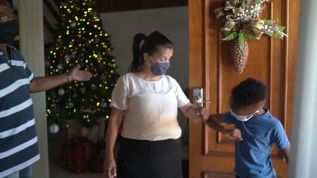 stockvideo's en b-roll-footage met familie die voor kerstmisgroet door grootouders in de deuropening thuis aankomt - sociale bijeenkomst