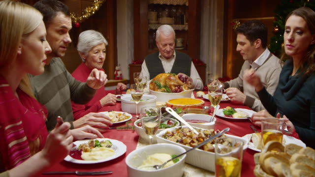 Family at Christmas dinner eating and talking video