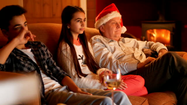 family at christmas watching television - christmas movie video stock e b–roll