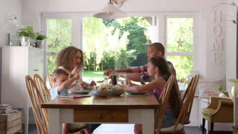 vídeos de stock e filmes b-roll de family at home eating meal in dining room together - family