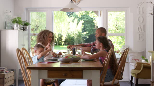 family at home eating meal in dining room together - family home video stock e b–roll