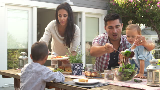 family at home eating outdoor meal in garden shot on r3d - family home video stock e b–roll