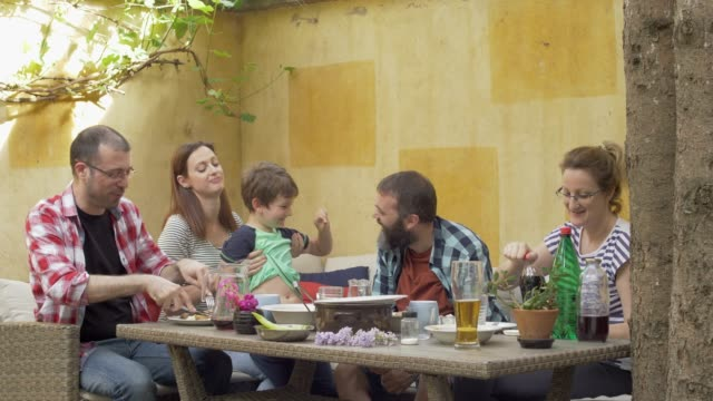 Family at home eating outdoor meal in garden