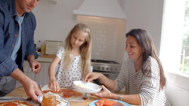 Famille à la maison dans la cuisine faire des Pizzas ensemble - Vidéo