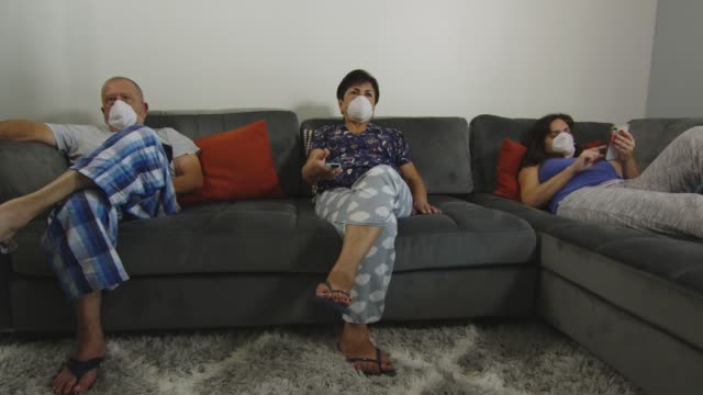 Family at home wearing face masks during quarantine video