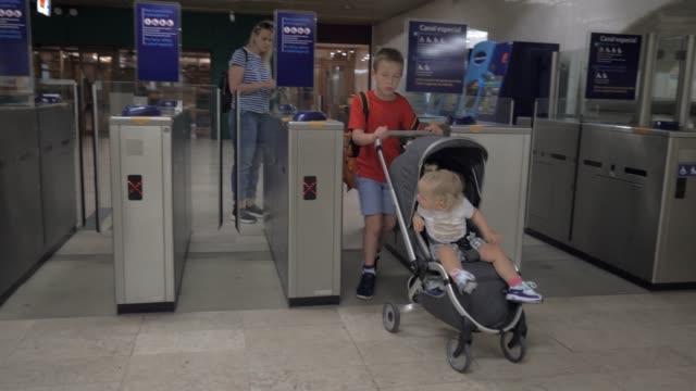 Family at turnstile in underground
