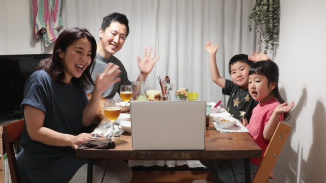 family attending online video meeting and having dinner together at home - video call with family stock videos & royalty-free footage