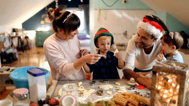 Family baking Christmas cookies Video of a cute young family baking Christmas cookies during Christmas holidays, dressed as Santa, an Elf and Reindeer cookie stock videos & royalty-free footage