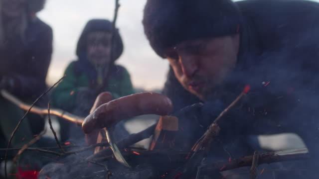 şenlik ateşinde aile pişirme yemeği. kış eğlencesi. şehir kıyısında - şenlik ateşi stok videoları ve detay görüntü çekimi