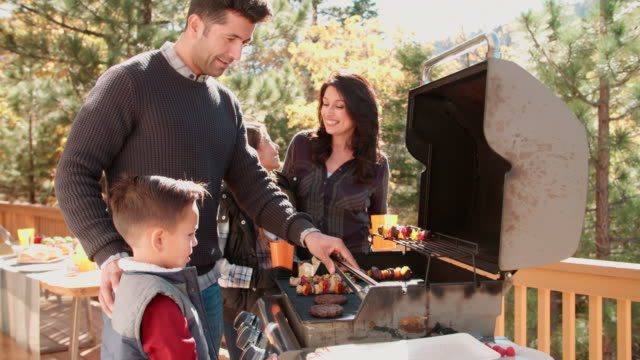 Family barbecuing on a deck in the forest video