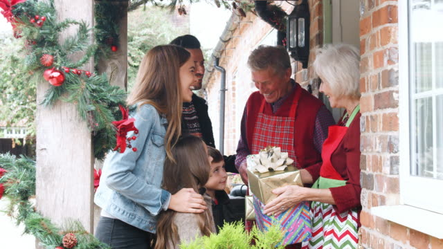 vídeos de stock e filmes b-roll de family being greeted by grandparents as they arrive for visit on christmas day with gifts - family christmas